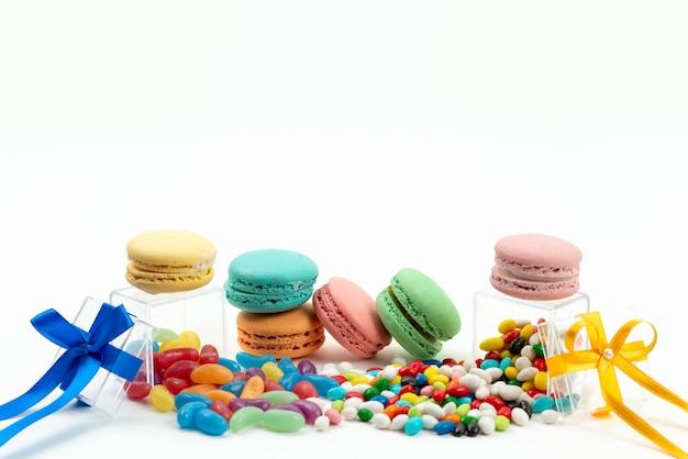 Französische macarons mit vorderansicht runden köstlich zusammen mit farbigen bonbons auf weißer kuchenkeksfarbe ab