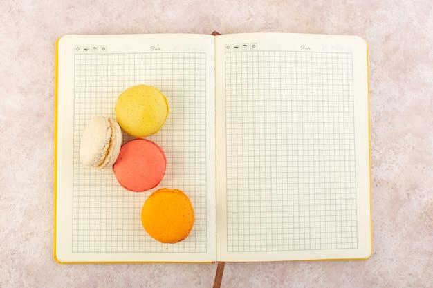 Französische macarons von oben auf dem heft und der rosa tischkuchen-kekszuckersüß