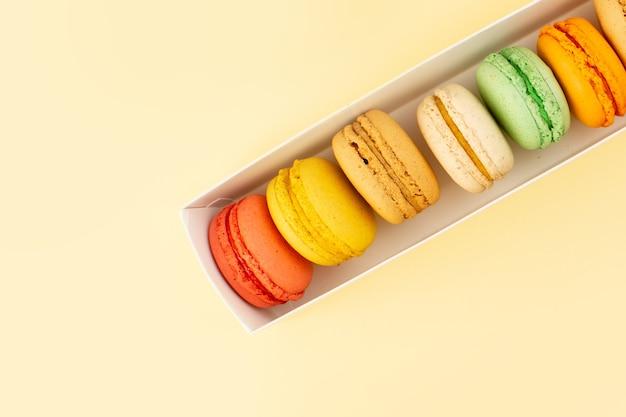 Französische macarons von oben, ausgekleidet auf dem gelben tischkuchen-kekszuckersüß