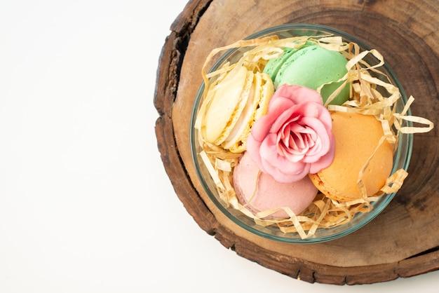 Französische macarons von oben in der runden glasplatte auf brauner hölzerner kuchenkeksfarbe