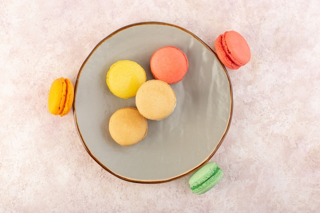 Französische macarons von oben in der runden platte auf dem süßen kekszucker des rosa tischkuchens