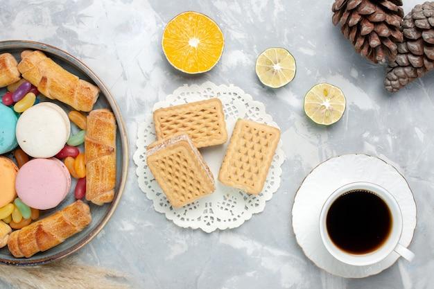 Französische macarons von oben mit bagels und einer tasse tee auf weiß