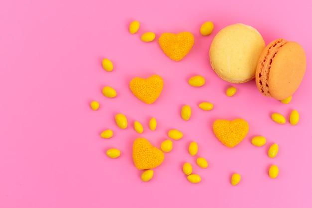 Französische macarons von oben mit gelben bonbons auf rosa kuchenkuchenfarbe
