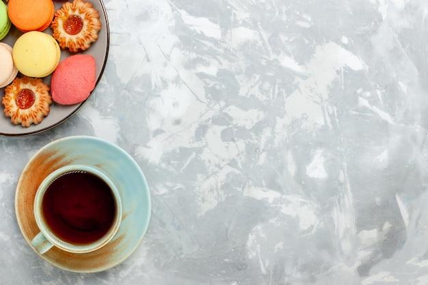 Französische macarons von oben mit keksen und tee auf hellweißer oberfläche