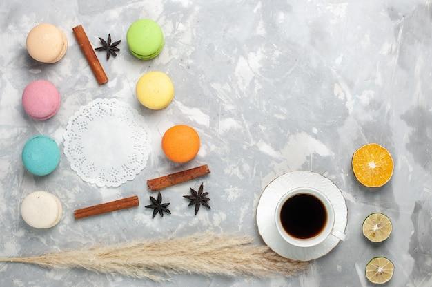 Französische macarons von oben mit tasse tee auf hellweißem schreibtisch