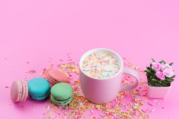 Französische macarons von oben, zusammen mit bunten bonbonpartikeln, alle auf rosa, bodenkuchenförmigem kekszuckersüß