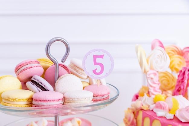 Französische makronen auf einem tortenständer. schokoriegel mit macaron, kuchen, käsekuchen, cake pops. bunte makronen auf serviertablett. dekorativer süßer geburtstagstisch in leuchtenden farben gelb, weiß und rosa.