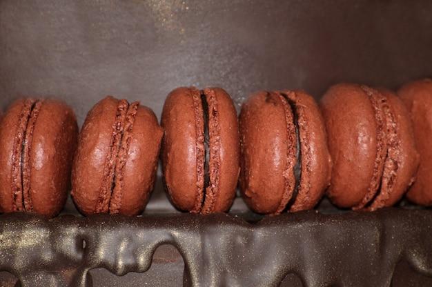 Französische makronen auf schokoladenhintergrund