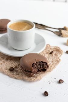 Französische makronen der kaffeetasse und der schokolade auf einer weißen hölzernen rückseite