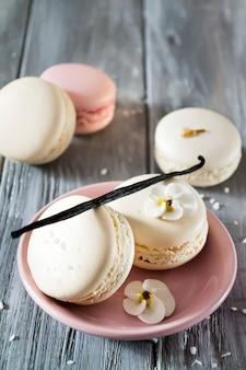 Französische makronen in einer platte mit vanillestock