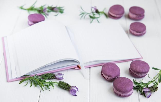 Französische makronen, sauberes notizbuch und lavendelblumen