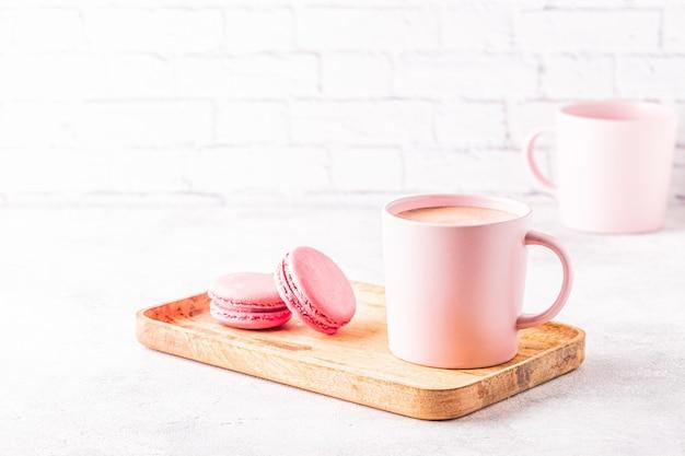 Französische makronen und eine tasse kaffee auf einem holztablett.