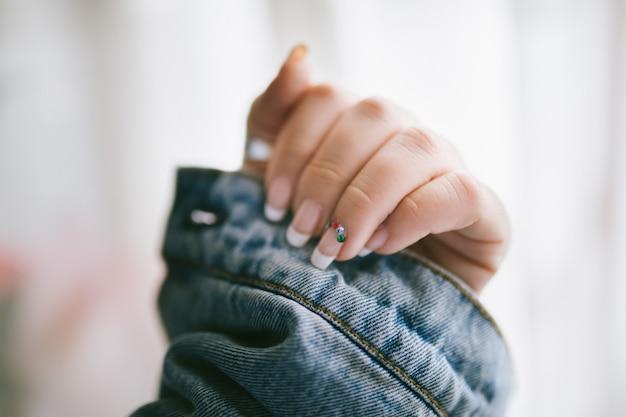 Französische maniküre der eleganten und langlebigen frau mit bunten perlen. frau, die ihren arm berührt. damenhand mit französischer maniküre.