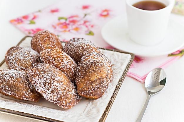 Französische plätzchen madeleine und tee in der weißen schale. konzept romantisches frühstück.