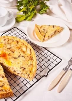 Französische quiche-torte mit huhn und pilzen