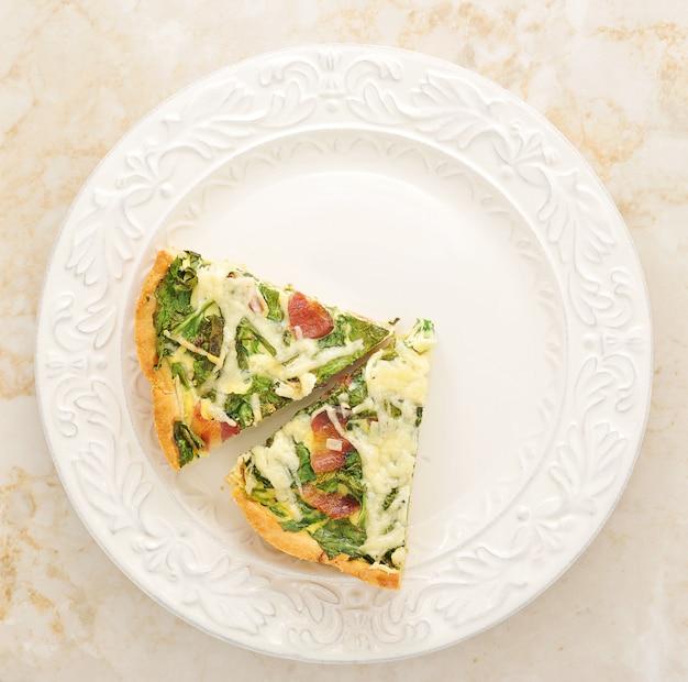 Französische quichetorte mit ei, käse und spinat auf der platte. ansicht von oben