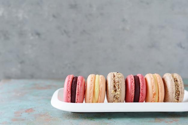 Französische sortierte macarons backt auf einem rechteckigen teller zusammen. bunte kleine französische kuchen. ansicht von oben.