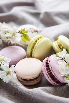 Französische süße makronen bunte vielfalt auf grauem textilhintergrund mit frühlingsblüte