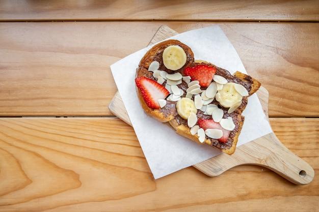 Französische toast mit schokoladenbananenerdbeere und -mandel auf dem holztisch