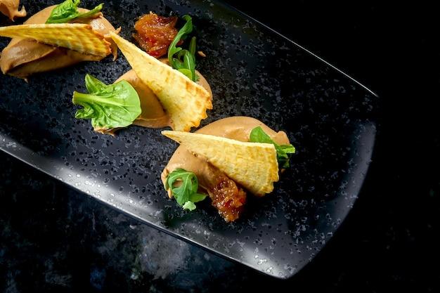 Französische vorspeise - hühnerpastete mit häppchen mit zwiebelconfit, serviert in einem schwarzen teller auf einem dunklen marmortisch. restaurant essen
