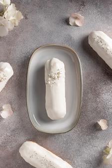 Französische weiße schokoladen-eclairs und hortensienblüten