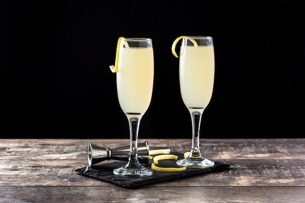Französischer 75-cocktail im glas auf holztisch und schwarzem hintergrund