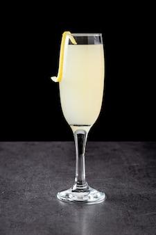 Französischer 75er cocktail im glas auf schwarzem hintergrund