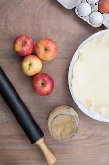 Französischer apfelkuchen und bestandteile über rustikalem hintergrund