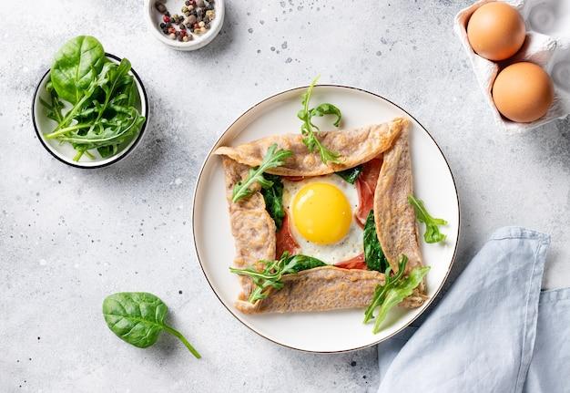Französischer buchweizenkrepp mit ei, schinken und spinat