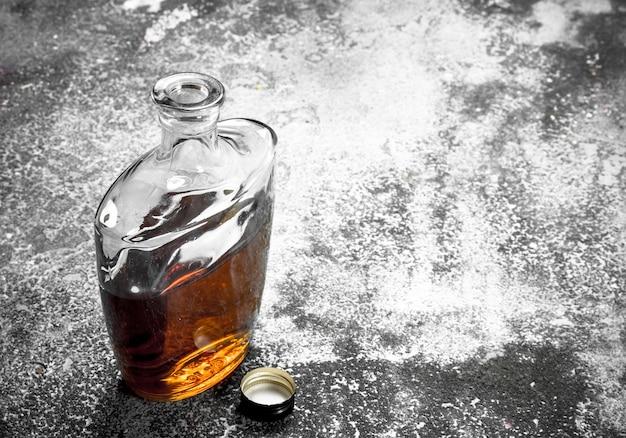 Französischer cognac in der flasche. auf einem rustikalen hintergrund.