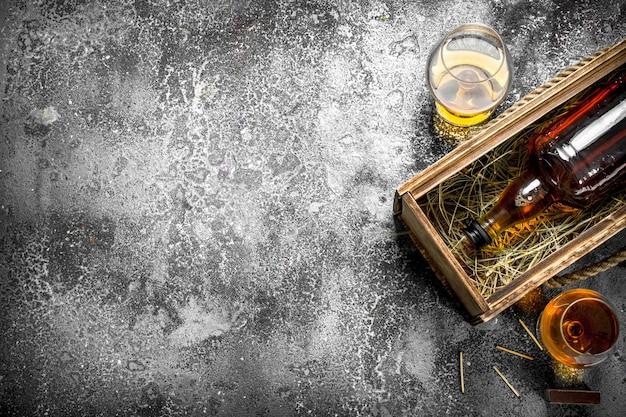 Französischer cognac in einer alten schachtel. auf einem rustikalen hintergrund.
