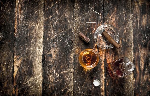 Französischer cognac mit einer zigarre. auf einem hölzernen hintergrund.