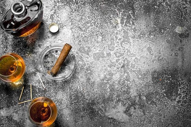 Französischer cognac mit einer zigarre. auf einem rustikalen hintergrund.