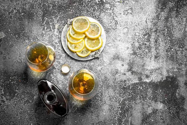 Französischer cognac mit zitrone. auf einem rustikalen hintergrund.