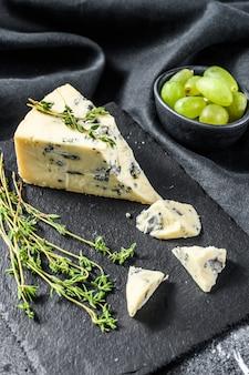 Französischer gorgonzola-käse mit trauben. schwarzer hintergrund. draufsicht