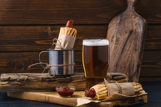 Französischer hot dog mit bier im rustikalen stil. straßenessen.