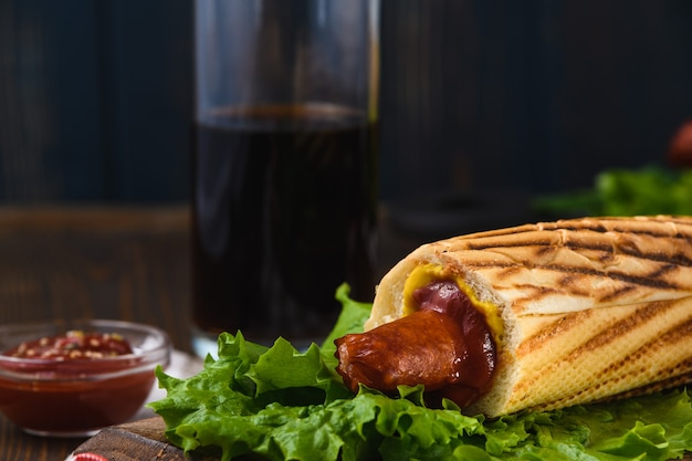 Französischer hot dog mit kräutern und einem getränk im rustikalen stil. straßenessen.