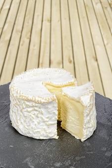 Französischer käse platziert auf einen schwarzen schiefer
