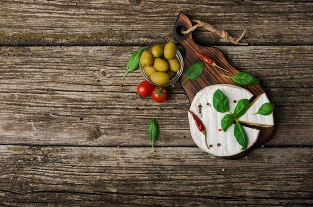Französischer käse - runder camembert mit basilikumblättern, paprika und oliven auf einem hölzernen hintergrund. draufsicht