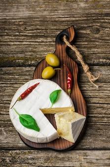 Französischer käse - runder camembert mit basilikumblättern, paprika und oliven