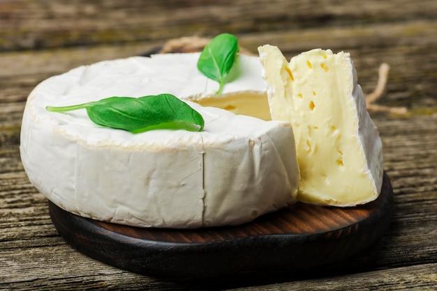 Französischer käse - runder camembert mit basilikumblättern