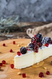 Französischer käsebriekäse, camambert, honig, marmelade und kiefernnüsse auf hölzerner käseplatte. schärfen