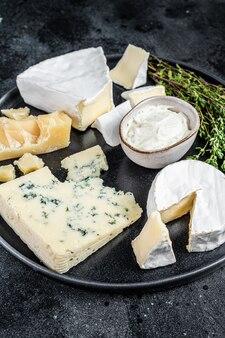 Französischer käseteller. camembert, brie, gorgonzola und blauschimmelkäse. schwarzer hintergrund. ansicht von oben.