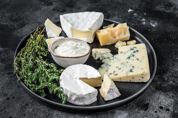 Französischer käseteller. camembert, brie, gorgonzola und blauschimmelkäse. schwarzer hintergrund. draufsicht.