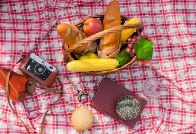 Französischer korb mit obst, baguette, buch, retro-kamera auf einer karierten roten tischdecke im freien