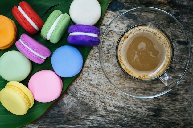 Französischer macaron und tasse heißen kaffee auf holztisch