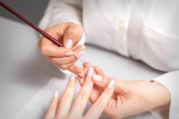 Französischer maniküre-maniküre-meister, der weißen lack auf der nagelspitze mit einem dünnen pinsel nahaufnahme zeichnet