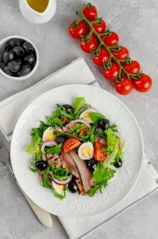 Französischer salat nicoise mit thunfisch, ei, grünen bohnen, tomaten, oliven, salat, zwiebeln und sardellen auf einem grauen betonhintergrund. gesundes essen.