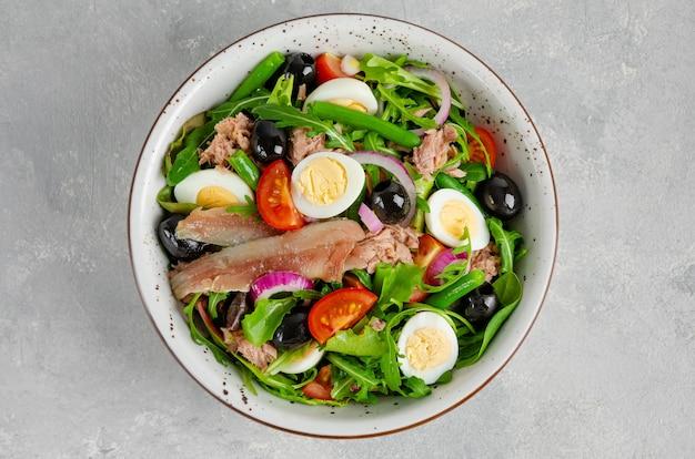 Französischer salat nicoise mit thunfisch, tomaten, oliven, salat und mehr auf einer schüssel auf betonhintergrund