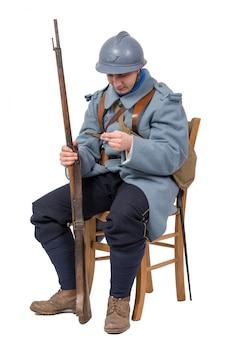 Französischer soldat, der auf dem stuhl, den brief lokalisiert auf weiß lesend sitzt